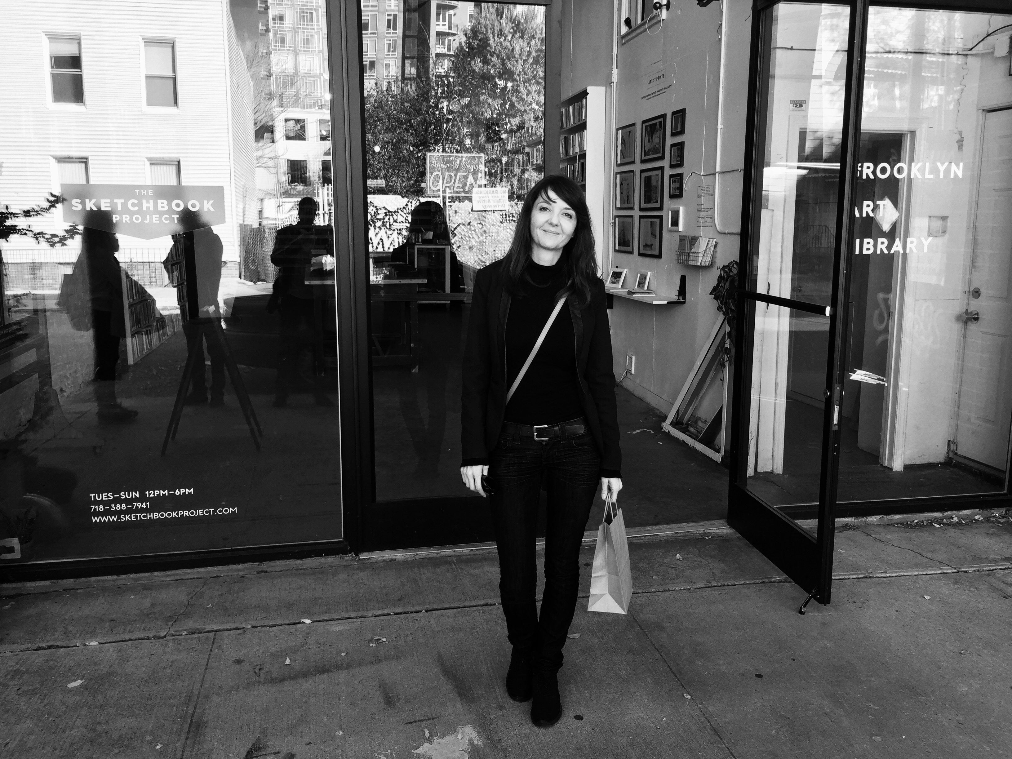 Black and white photo of artist Anja Studer standing in front of the library holding a shopping bag.